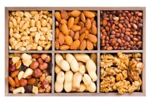 various dried nuts in wooden box isolated on white background